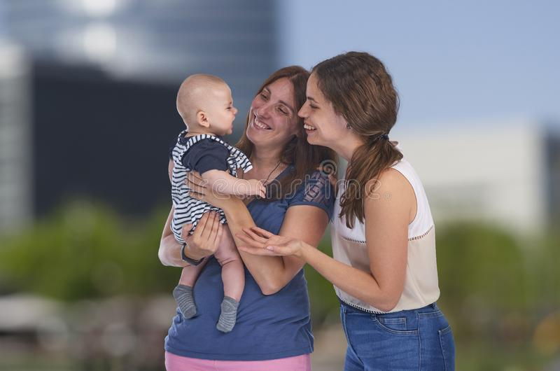 Den homosexuella familjen, unga lesbiska mödrar med deras behandla som ett barn Lesbisk förälskelse royaltyfria bilder
