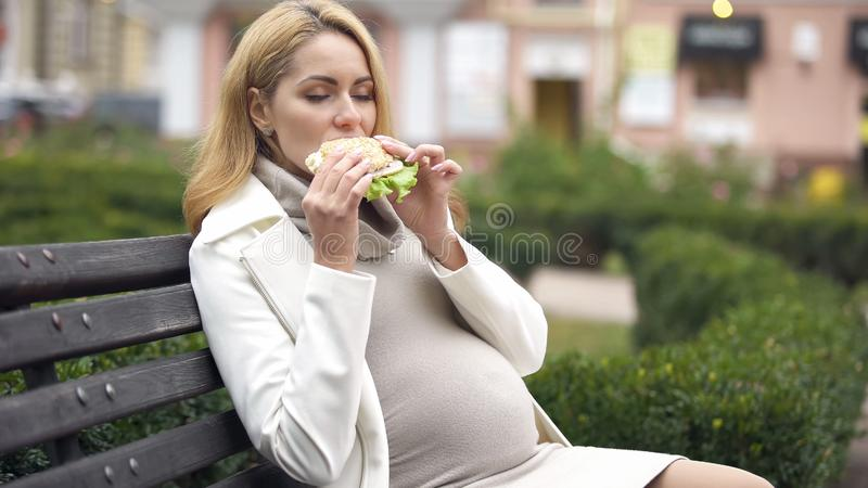 Den hungriga gravida kvinnan som tycker om den läckra hamburgaren som sitter på bänk parkerar in arkivbilder