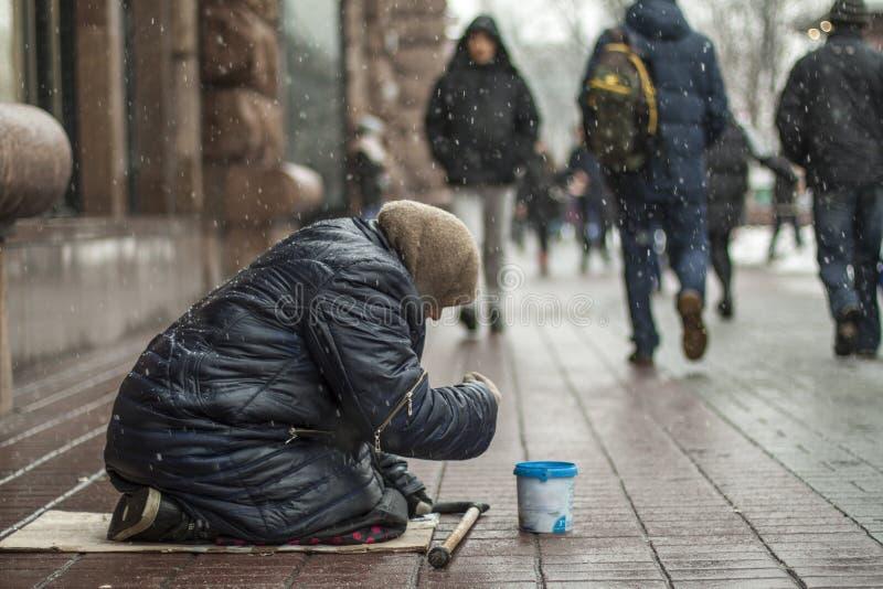 Den hungriga hemlösa tiggarekvinnan tigger för pengar på den stads- gatan i staden från folk som förbi går royaltyfri fotografi