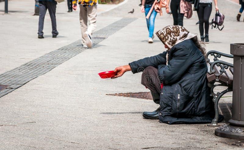 Den hungriga hemlösa tiggarekvinnan tigger för pengar på den stads- gatan i staden från folk som förbi går, det sociala dokumentä royaltyfri fotografi