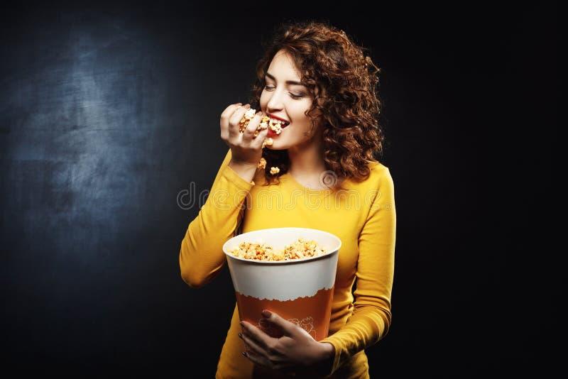 Den hungriga kvinnan äter handfullpopcorn, medan vänta på film arkivfoton