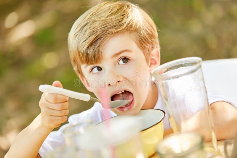 Den hungriga pojken äter mysli för frukost arkivfoton