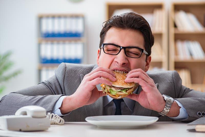 Den hungriga roliga affärsmannen som äter skräpmatsmörgåsen fotografering för bildbyråer