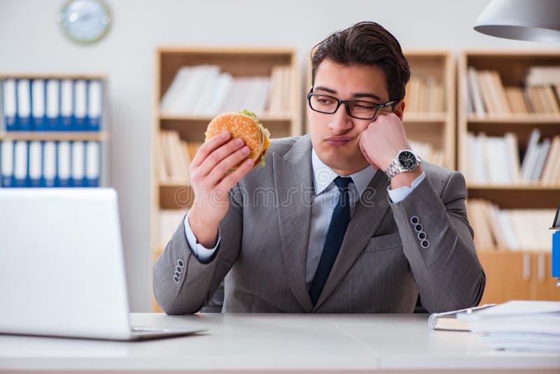 Den hungriga roliga affärsmannen som äter skräpmatsmörgåsen royaltyfri foto