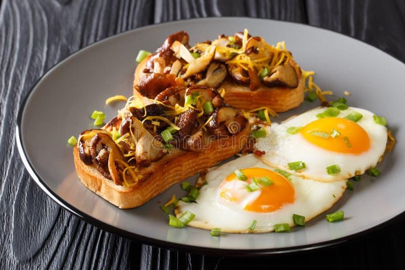 Den hurtiga frukosten av stekt rostat bröd med shiitakechampinjoner och cheddarost tjänade som med äggnärbild på en platta horiso royaltyfri fotografi