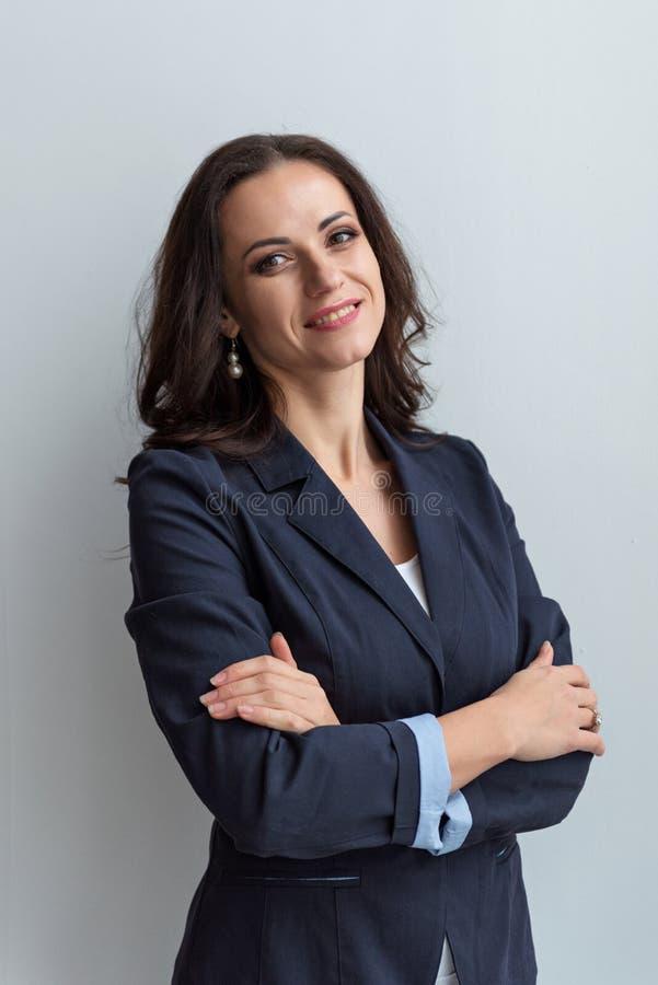Den i halvfigur ståenden av en le affärskvinna i ett omslag med armar korsade arkivfoton