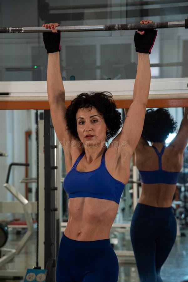 Den i halvfigur ståenden av en ung muskulös flicka med en blå klänningsliv, använder hon multipower i idrottshallen arkivbilder