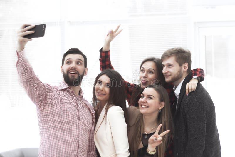 Den idérika affärsgruppen tar selfies i ett modernt kontor royaltyfri bild
