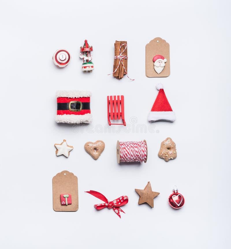 Den idérika julorienteringen som göras av hantverkpappersetiketter, kakor, röd jul, övervintrar garnering: Jultomten hatt, släde, arkivfoto