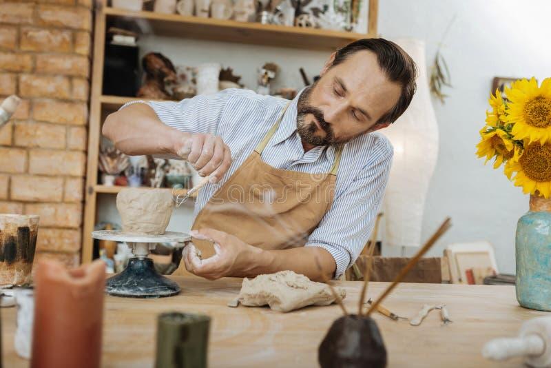 Den idérika keramikern som luktar arom, klibbar arbete med krukmakerihjulet arkivbild