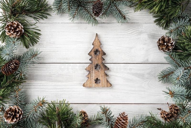 Den idérika orienteringsramen gjorde av julgranfilialer och sörjer kottar på vit bakgrund med statyetten av träjulgranen royaltyfri fotografi