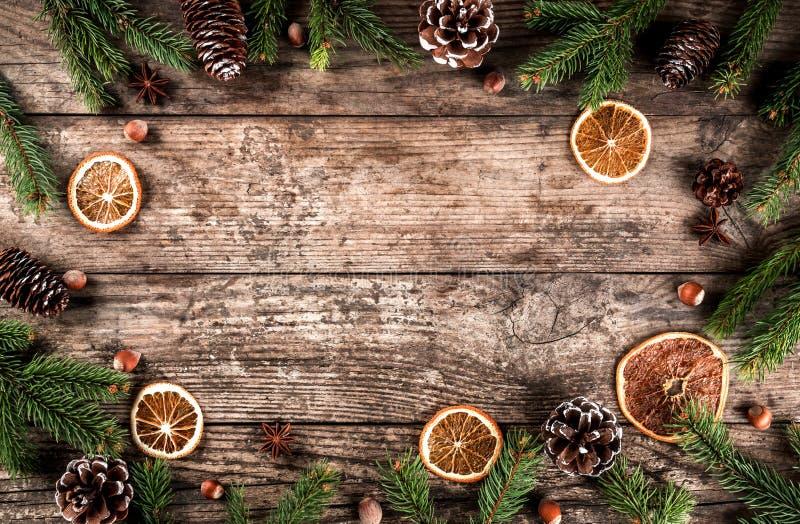 Den idérika orienteringsramen som göras av julgranfilialer, granen, skivor av apelsinen, sörjer kottar, snöflingor på träbakgrund royaltyfria foton