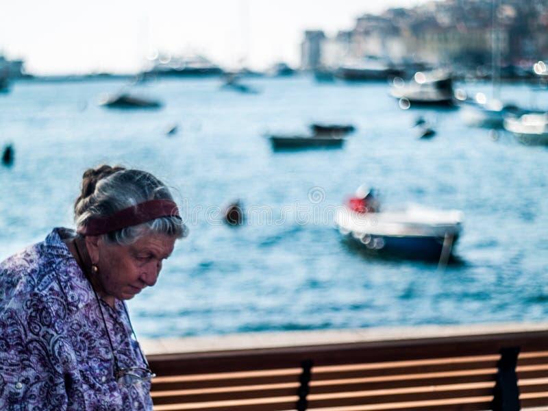 Den idérika platsen av en gammal kvinna från Rovinj, Kroatien Centraleuropa i middagar, med härlig fartygbokeh klumpa ihop sig an royaltyfri fotografi