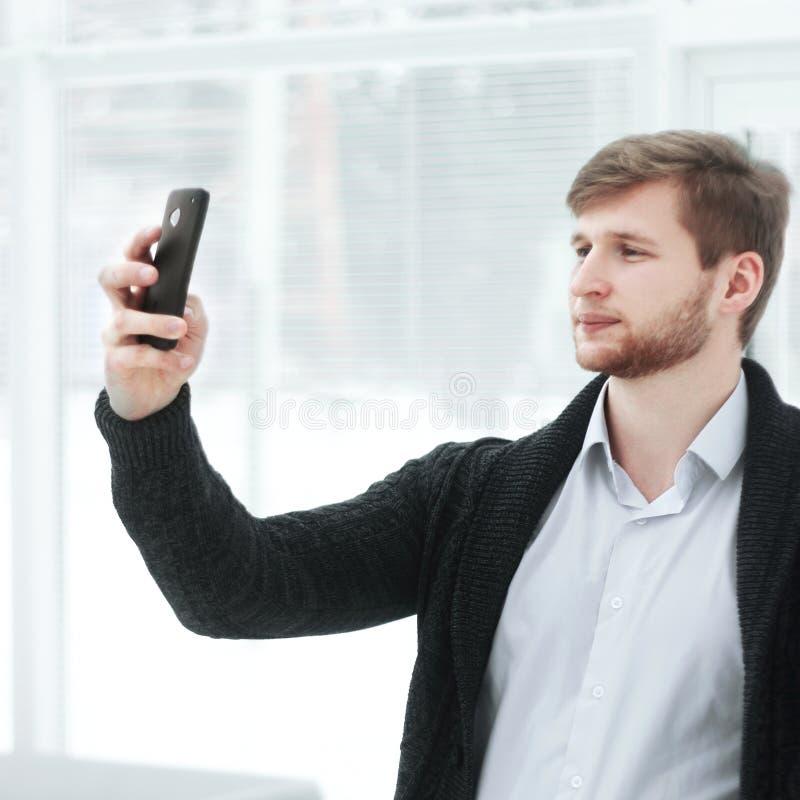 Den idérika unga mannen tar en selfie i ett modernt kontor royaltyfri fotografi
