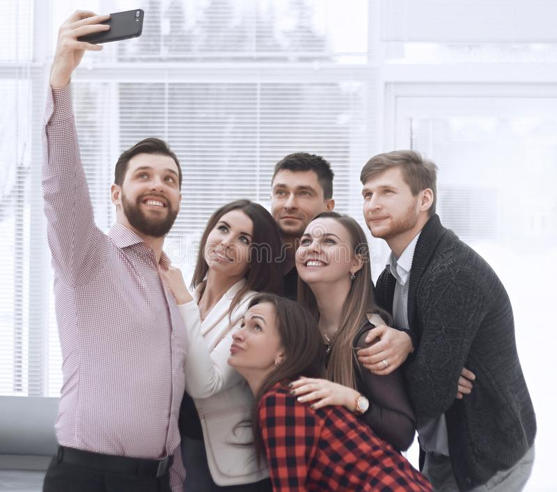 Den id?rika aff?rsgruppen tar selfies i ett modernt kontor royaltyfria foton