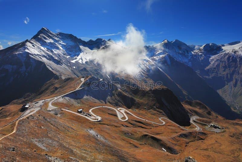 Den ideala huvudvägen spolar höjdpunkt i bergen royaltyfri bild