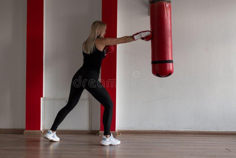Den idrotts- blondinen för den unga kvinnan i en svart T-tröja i svart sportdamasker i gymnastikskor i röda boxas handskar står royaltyfri bild