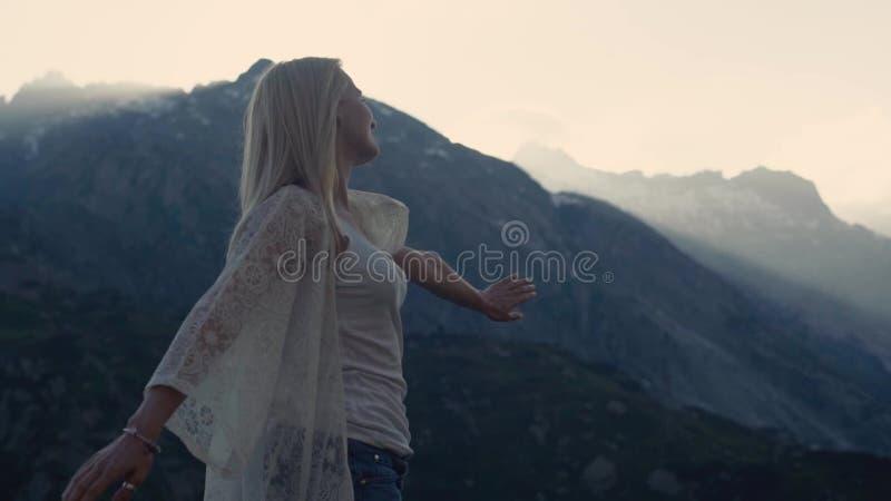Den idrotts- flickan dansar på överkanten av världen, de härliga bergen och den blåa himlen på horisonten Hon försöker till
