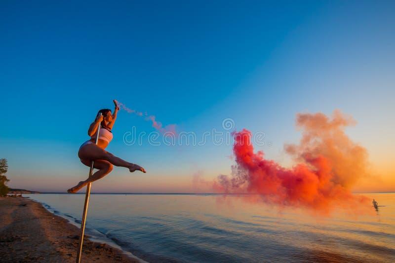 Den idrotts- flickan klättrade på en bärbar pylon på stranden och rymmer en röd rökgranat Sand solnedgång, strand royaltyfria bilder