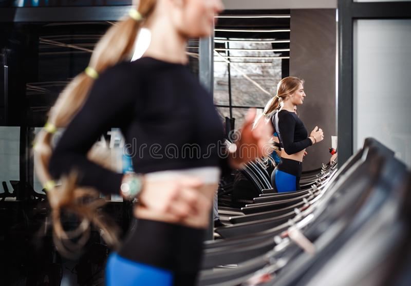 Den idrotts- flickan med iklätt långt blont hår en sportswear kör på trampkvarnen i den moderna idrottshallen royaltyfri fotografi