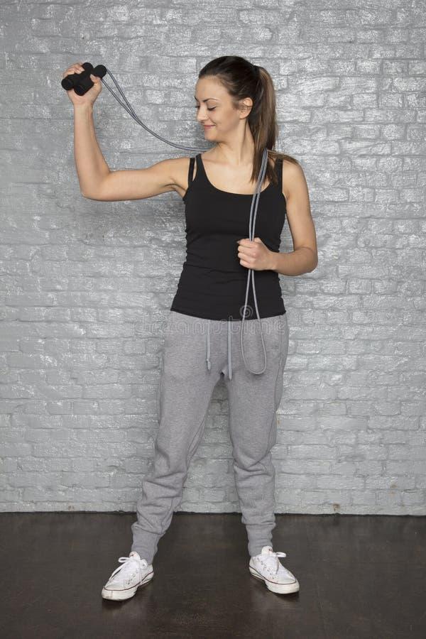 Den idrotts- flickan rymmer ett rep i hennes hand arkivbild