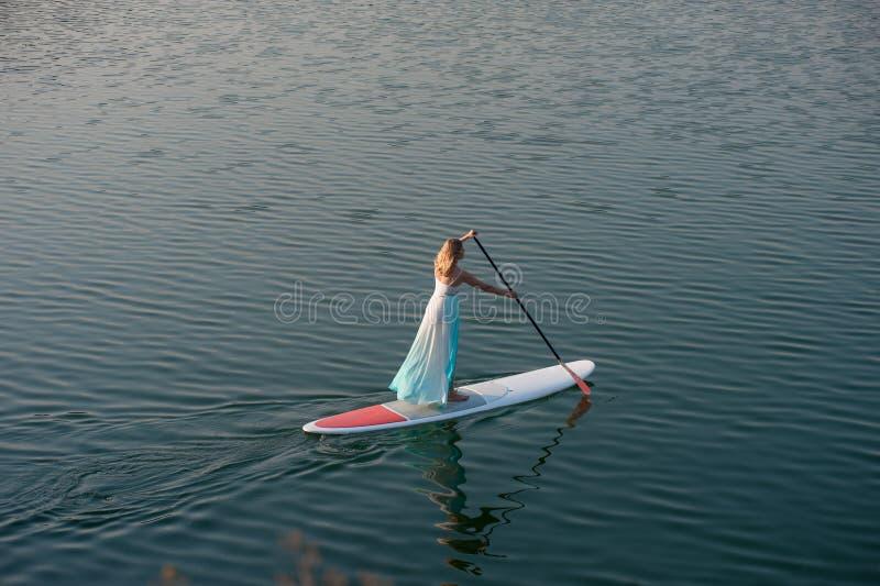 Den idrotts- flickan står upp paddleboard01 royaltyfria foton