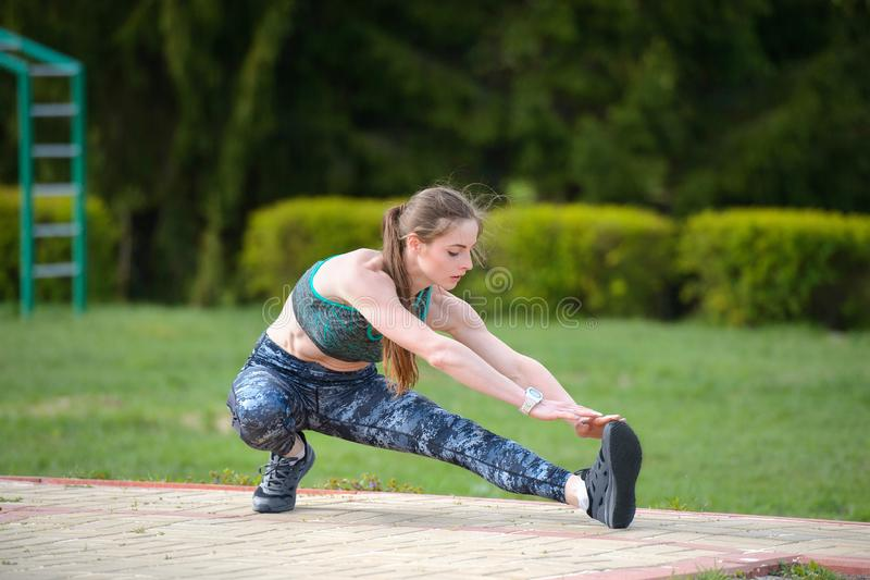 Den idrotts- flickan utför knäsena och sträckningsövningar royaltyfria foton