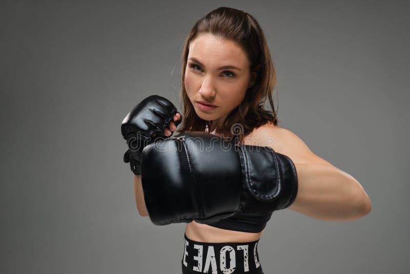 Den idrotts- kvinnan i boxninghandskar öva karate i studio arkivfoton