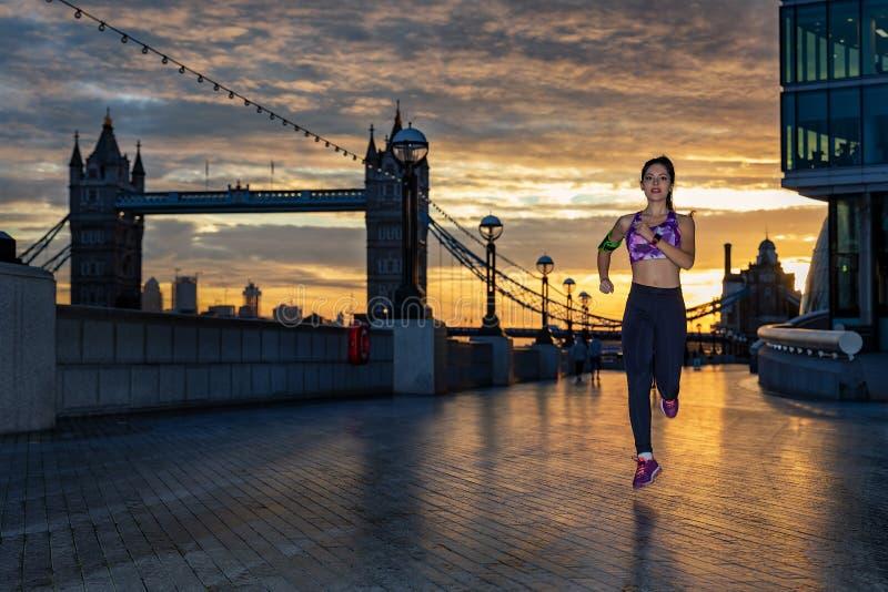 Den idrotts- kvinnan kör under soluppgång i staden royaltyfria foton