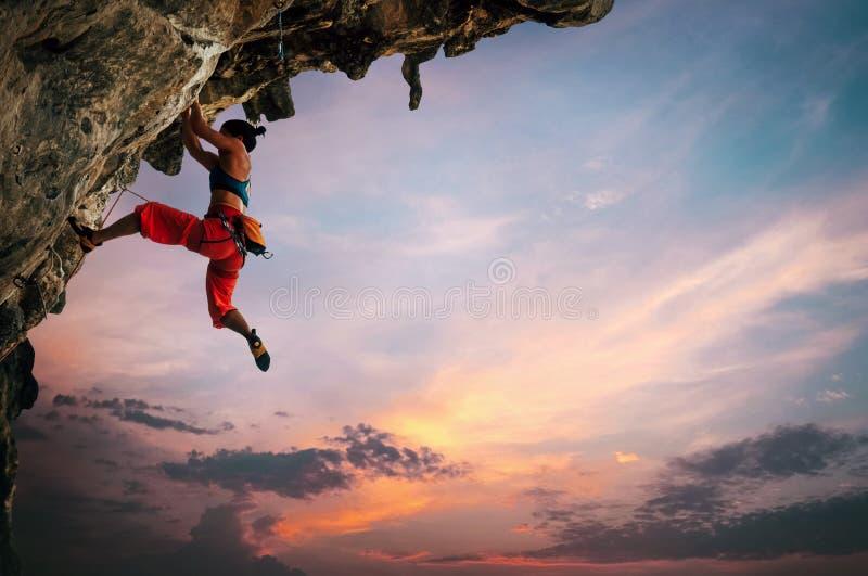 Den idrotts- kvinnan som kl?ttrar p? den h?ngande ?ver klippan, vaggar med solnedg?nghimmelbakgrund royaltyfria bilder