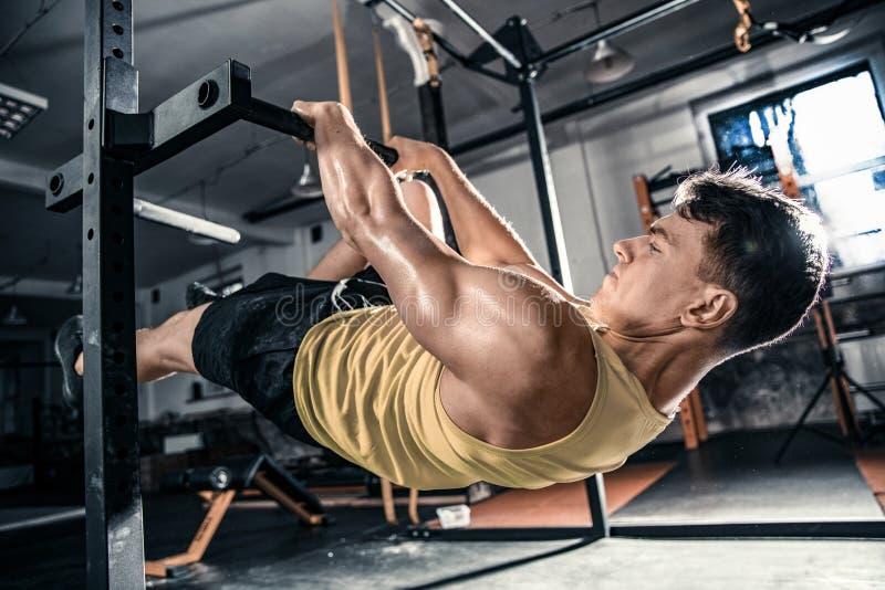 Den idrotts- mannen lyfter hans kropp på hans händer fotografering för bildbyråer