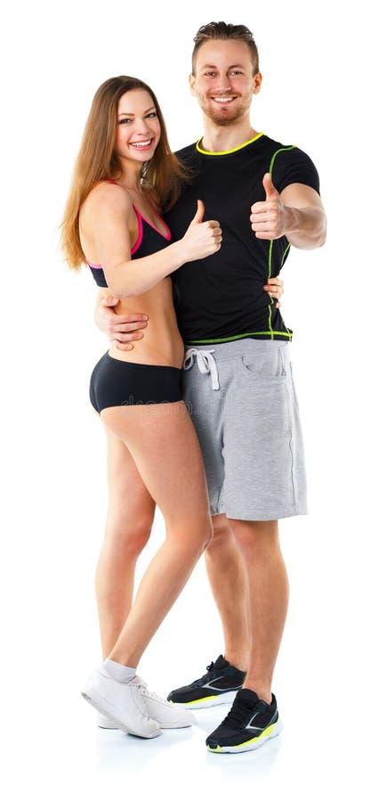 Den idrotts- mannen och kvinnan efter kondition övar med tummar upp på arkivbild