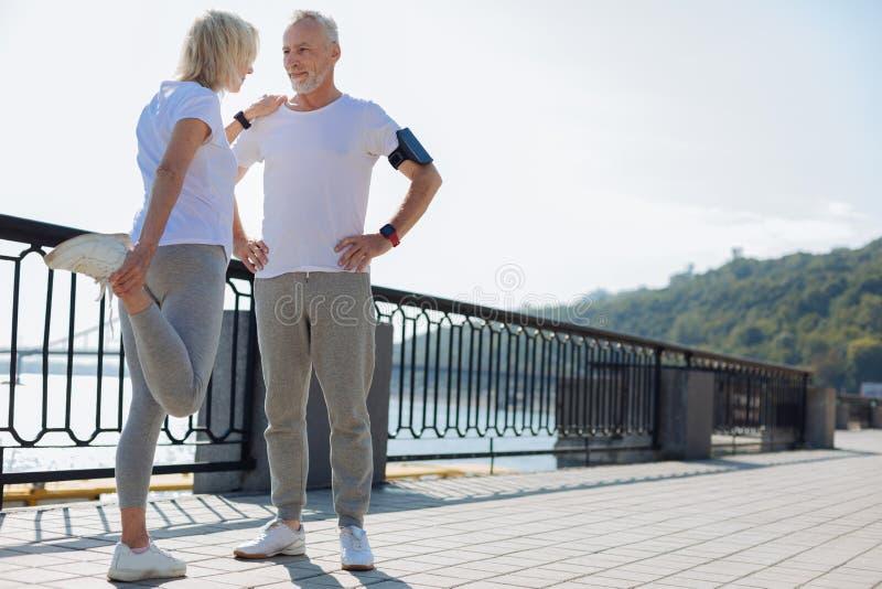 Den idrotts- mannen som ger jämvikt för kvinnan som gör sträckning, övar royaltyfri foto