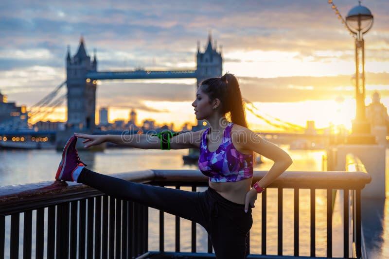 Den idrotts- stadskvinnan gör hennes elasticiteter framme av tornbron i London royaltyfri fotografi