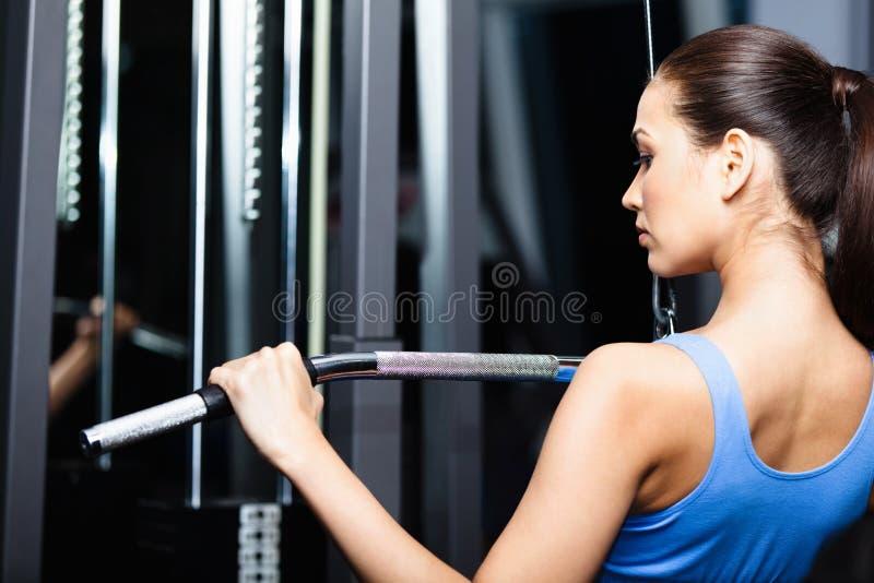 Den idrotts- unga kvinnan fungerar ut på idrottshallutbildning royaltyfri fotografi
