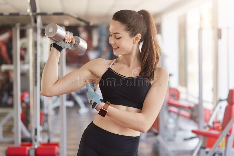 Den idrotts- unga kvinnan med simulatorer på bakgrund, rymmer hanteln i hand och visar hennes biceps, ser på hennes arm, har ge royaltyfri foto