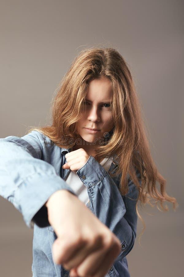 Den iklädda aggressiva brunhåriga flickan en vit t-skjorta och jean rymmer händer i nävar på en grå bakgrund arkivfoton