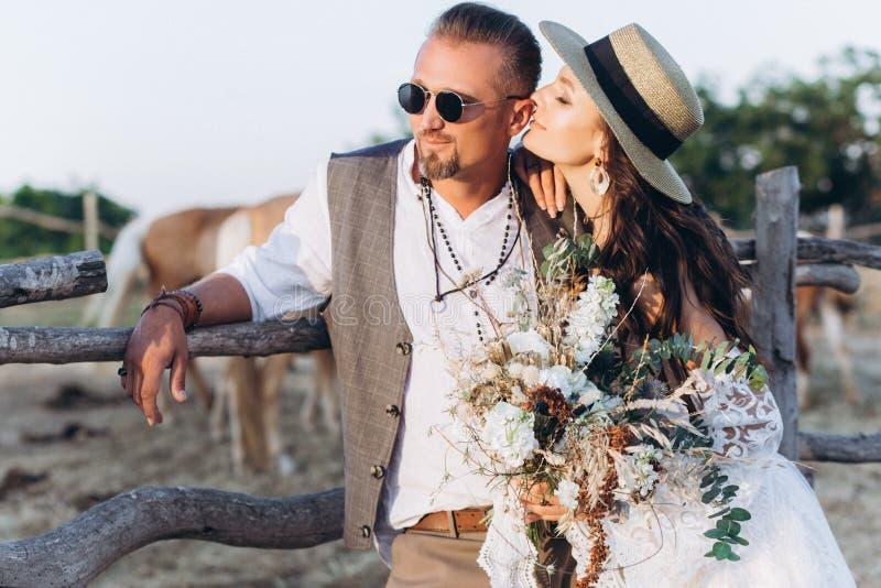 Den iklädda brudgummen stilen av bohoen kysser försiktigt bruden royaltyfria foton