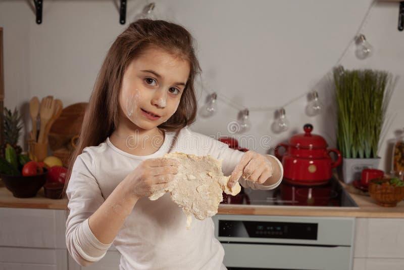 Den iklädda härliga lilla flickan en vit blus gör en deg för att baka ett bröd på ett kök royaltyfria foton