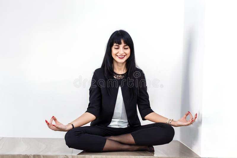 Den iklädda härliga unga kvinnan en svart affärsdräkt som i regeringsställning sitter i lotusblommaposition på ett golv och att l arkivbilder