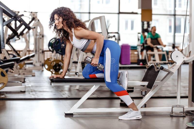 Den iklädda idrotts- lockiga flickan en sportswear gör övning på bänken med hantlar för triceps i den moderna idrottshallen royaltyfria foton