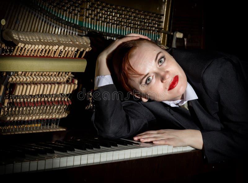 Den iklädda kvinnliga musikern en dräkt för man` s ligger på ett pianotangentbord arkivfoto