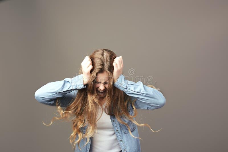 Den iklädda ledsna brunhåriga flickan en vit t-skjorta och jean rymmer hennes händer på hennes huvud och rop på en grå bakgrund royaltyfri fotografi