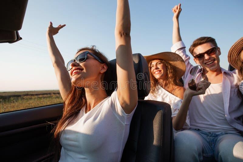 den iklädda Mörker-haired unga kvinnan en vit t-skjorta sitter en svart cabriolet med vänner på en sommardag arkivbilder