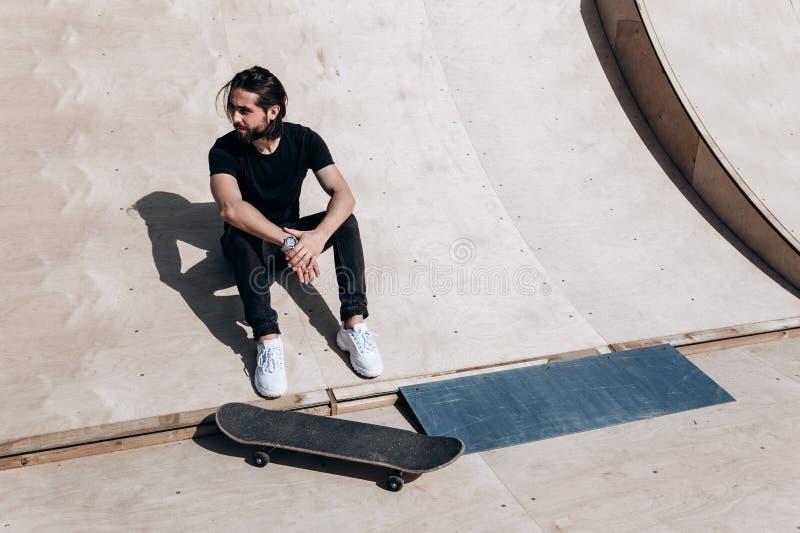 Den ikl?dda mannen den stilfulla tillf?lliga kl?derna sitter p? glidbanan bredvid skateboarden i en skridsko parkerar p? royaltyfri bild