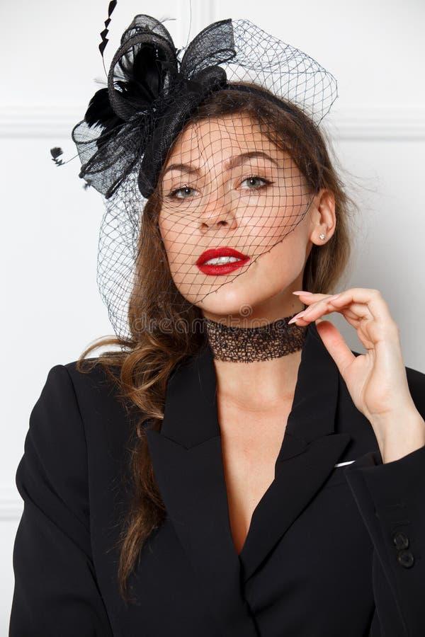 Den iklädda slanka charmiga flickan en stilfull svart klänning och den trendiga hatten poserar lite på den vita bakgrunden royaltyfri bild