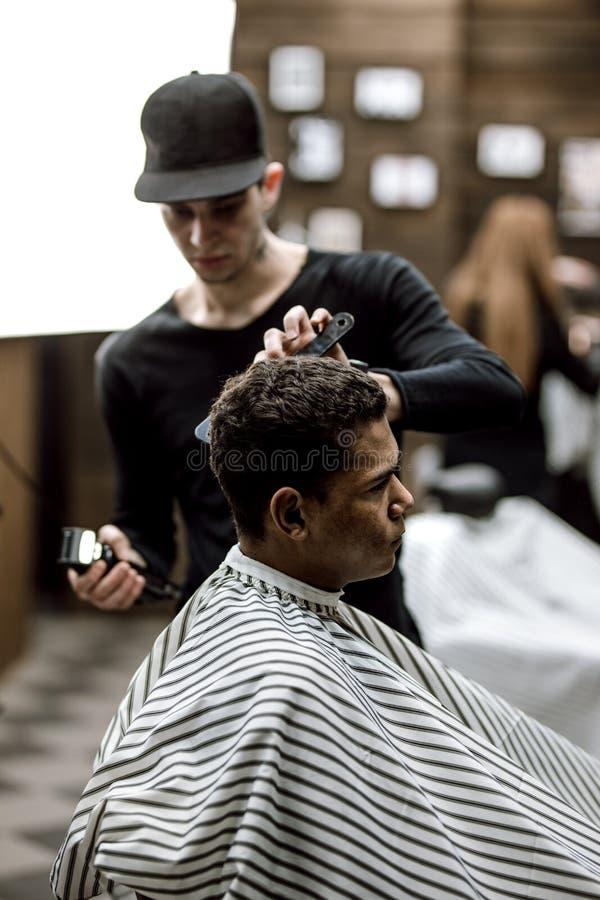 Den iklädda svarta kläderna för barberaren gör en baksida och sidor för hår för rakknivsnitt för en stilfull man som sitter i fåt arkivbilder