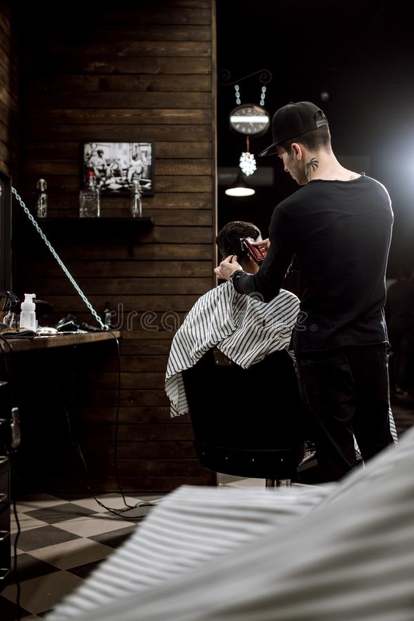 Den iklädda svarta kläderna för modebarberaren gör ett hår för rakknivsnitt för en stilfull svart-haired man i ett stilfullt royaltyfria foton