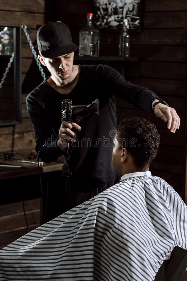 Den iklädda svarta kläderna för den stilfulla barberaren torkar mannens hår i en frisersalong royaltyfri bild