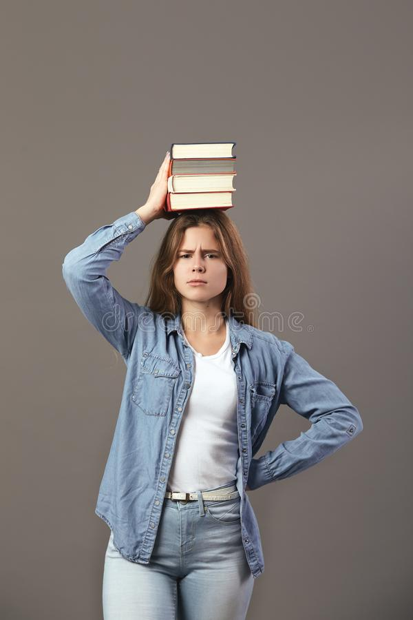 Den iklädda trevliga brunhåriga flickan en vit t-skjorta, jeans och jeans rymmer böcker på hennes huvud på en grå bakgrund royaltyfri foto